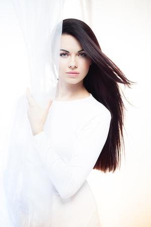 Frisse wind golft een stuk witte zijde stof achter een mooi jong meisje Stockfoto