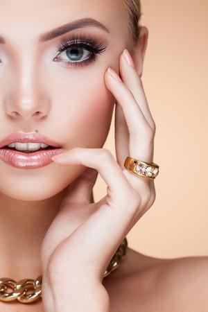 Junge Dame mit Luxus-Accessoires auf beige Hintergrund