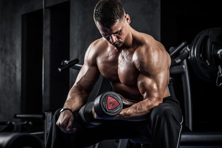 brutal: Brutal athletic man pumping up muscles with dumbbells