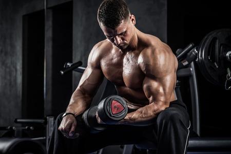 musculos: Hombre atlético Brutal bombeo de músculos con pesas