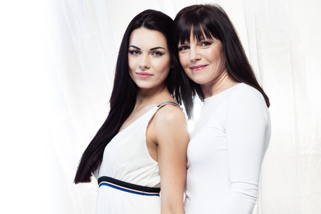 mature brunette: Happy smiling mother and daughter on white background
