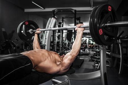 Brutal sportlichen Mann Aufpumpen Muskeln auf Bankdrücken Lizenzfreie Bilder