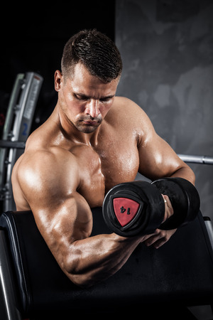 body pump: Brutal athletic man pumping up muscles with dumbbells