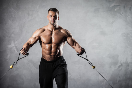 crossover: Brutal athletic man pumping up muscles on crossover