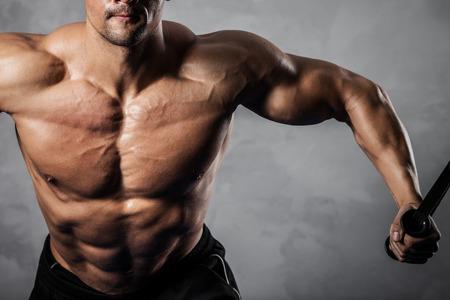 muskeltraining: Brutal athletischer Mann Aufpumpen Muskeln auf Crossover- Lizenzfreie Bilder