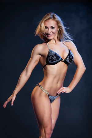 showing muscles: Smiling athletic woman in pink bikini showing muscles on dark background Stock Photo