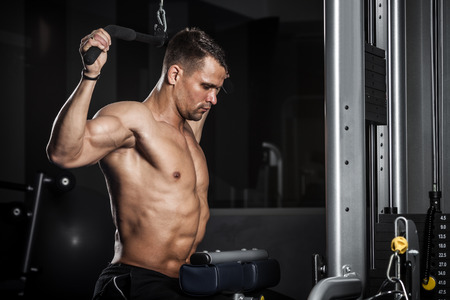 deltoids: Brutal athletic man pumping up muscles in a gym Stock Photo
