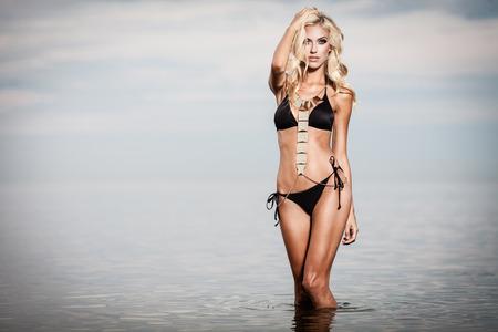 niñas en bikini: Mujer joven en bikini posando negro en un mar en calma, mientras que la puesta del sol