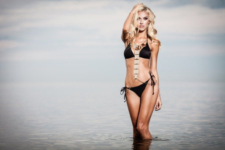 Young woman in black bikini posing in a calm sea while sunset