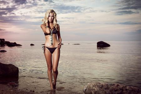 Young woman in black bikini posing in a calm sea while sunset