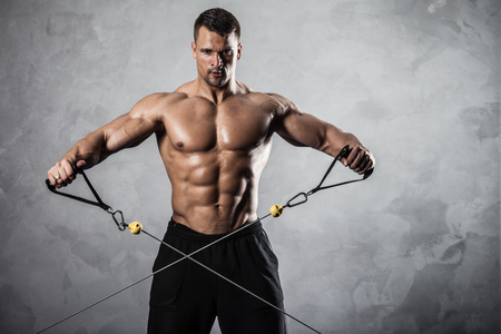 gym equipment: Brutal athletic man pumping up muscles on crossover