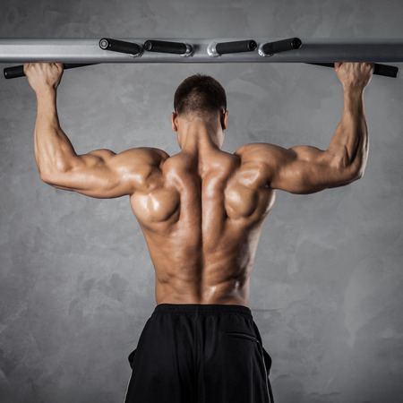 naked male body: Brutal athletic man making pull-up exercises on a crossbar Stock Photo