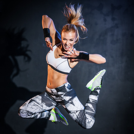Young woman jumps while making aerobics exercises on gray background Standard-Bild