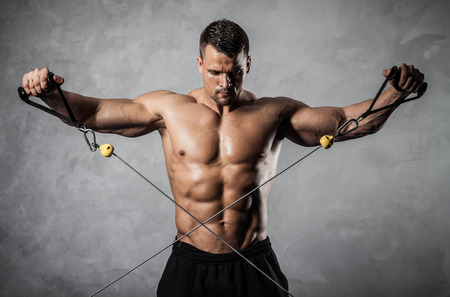power cable: Brutal athletic man pumping up muscles on crossover