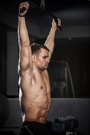 brutal: Brutal athletic man pumping up muscles in a gym Stock Photo