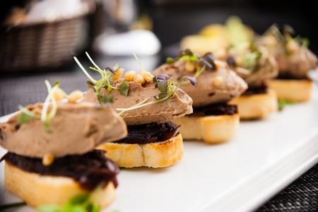 Zelfgemaakte eendenlever patee met ceder noten, gedroogde pruimen, bruschetta en rode ui jam Stockfoto