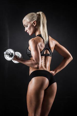Brutal athletische Frau Aufpumpen Muskeln mit Hanteln