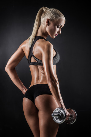 Brutal athletic woman pumping up muscles with dumbbells 版權商用圖片