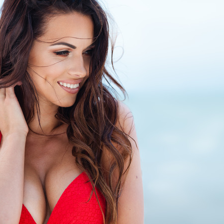 beach babe: Sexy brunette girl in red swimsuit posing on a beach