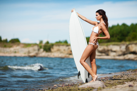 Sexy brunette girl in white swimsuit posing with a surfing board on a beach Stock Photo