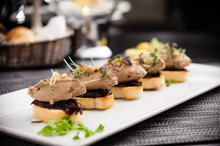 Homemade duck liver patee with cedar nuts, dried plums, bruschetta and red onion jam Stock Photo