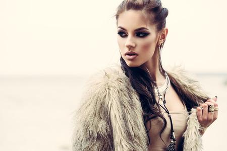 manteau de fourrure: Portrait d'une belle dame avec tottoos flash posant à l'extérieur près de la mer