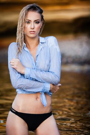 mojada: Mujer joven en camisa posando mojado en una arena rocas cerca del mar