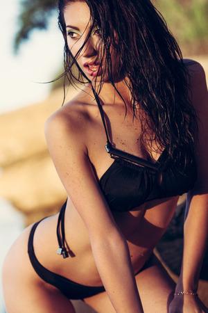 brunette: Mujer joven en bikini posando negro en una arena rocas cerca del mar