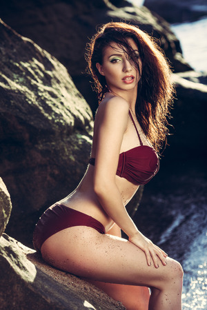 Young woman in red bikini posing on a sand rocks near the sea Stock Photo
