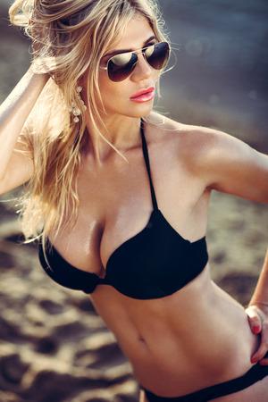 Young woman in black bikini and sunglasses posing on a beach