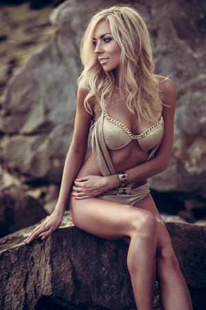 blonde bikini: Young woman in golden bikini posing on a sand rocks near the sea