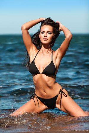 hot bikini: Sexy brunette girl in black bikini posing on a beach