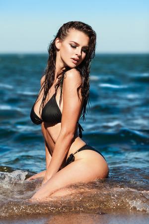Сексуальная брюнетка девушка в черном бикини позирует на пляже