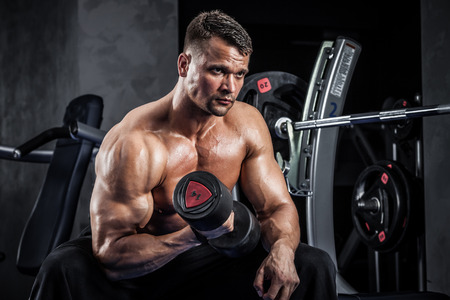 muscle guy: Brutal athletic man pumping up muscles with dumbbells