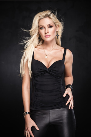 beautiful blonde: Sexy blond woman posing on dark background Stock Photo
