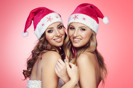 christmas hats: Girlfriends in Christmas hats on pink background Stock Photo