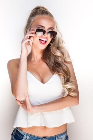 mujer elegante: Retrato de una joven glamour en gafas de sol posando cerca de la pared blanca