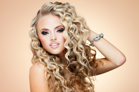 Young lady with luxury accessories on beige background