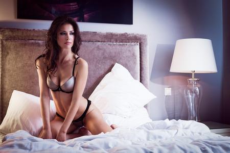 mujeres eroticas: Señora hermosa en lencería sexy se sienta en la cama Foto de archivo