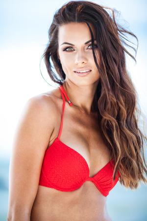 femme brune sexy: Sexy fille brune en maillot de bain rouge posant sur une plage