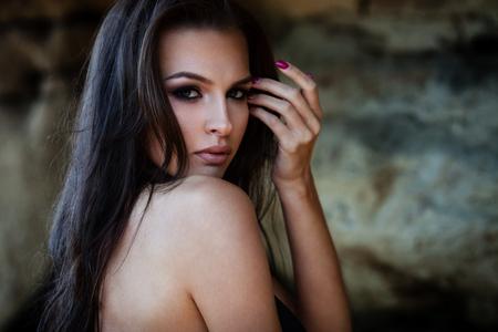 glamour model: Young woman in black bikini posing on a sand rocks near the sea