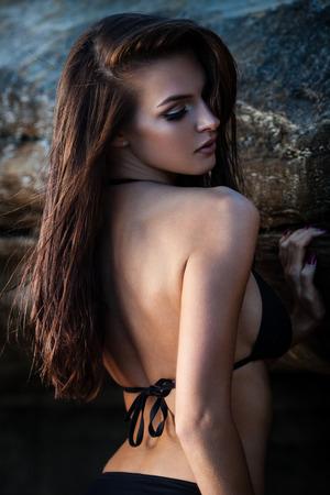 wet bikini: Young woman in black bikini posing on a sand rocks near the sea