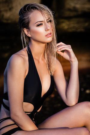 femme brune sexy: Jeune femme en noir bikini posant sur un sable rochers pr�s de la mer