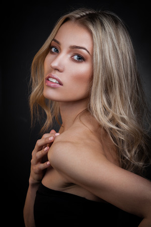 sexy woman: Sexy blond woman posing on dark background Stock Photo