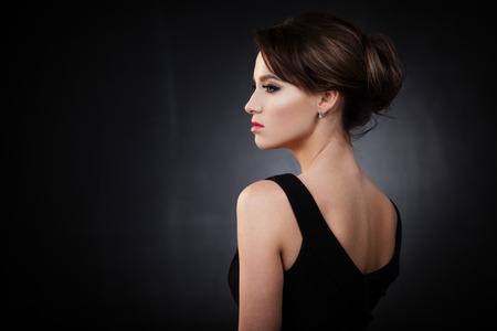 mujer morena atractiva que presenta en fondo oscuro