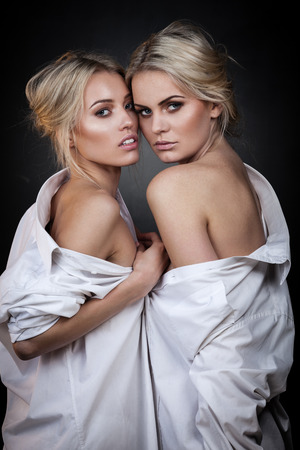 nude blonde: Two sexy girls in white shirts posing on dark background
