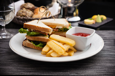 salted: Sandwich with fried eggs, bacon and lettuce served with french fries and ketchup