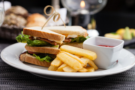 garnish: Sandwich with fried eggs, bacon and lettuce served with french fries and ketchup