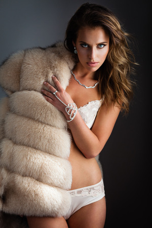 Beautiful lady in sexy lingerie poses in fur coat Stock Photo