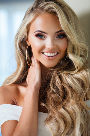 Portrait of attractive blond smiling woman in white Stock Photo